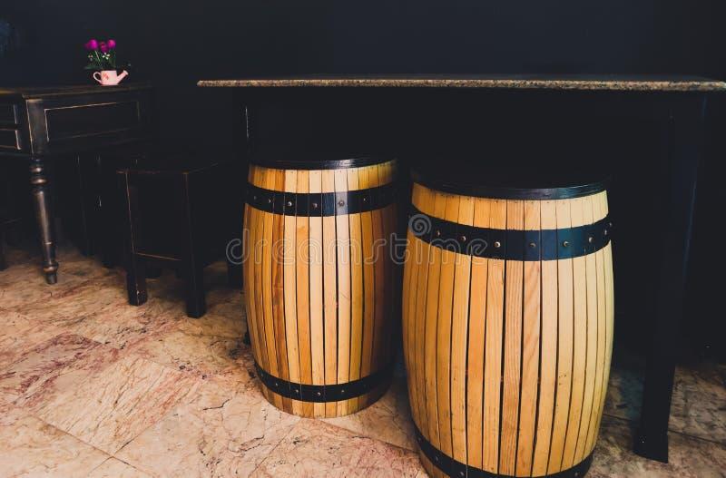 Het houten vat als zetelsplaats met marmeren lijst De reeks van zwart antiek houten stoelen en bureau in nabijgelegen Het binnenl stock foto