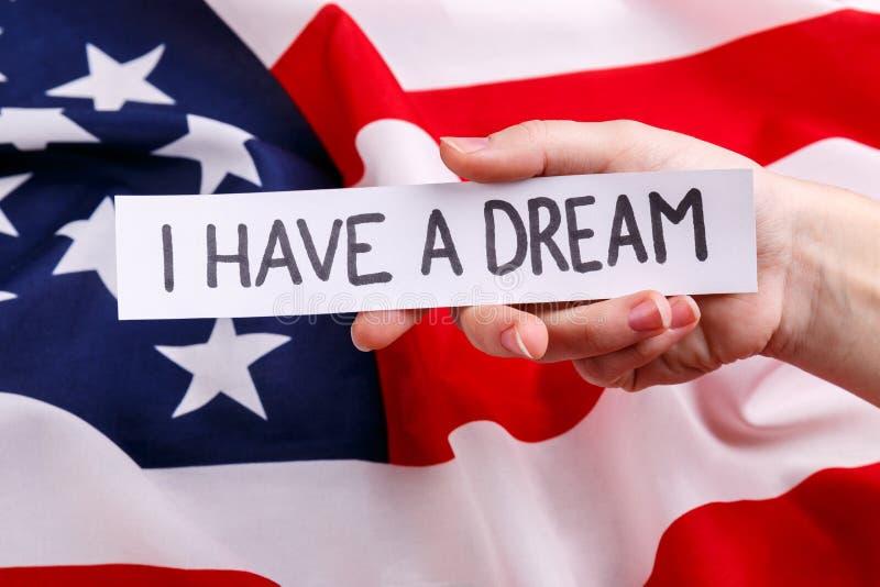 Het houvast een stuk van document met de inschrijving Martin Luther King Jr dag De achtergrond van de Amerikaanse vlag royalty-vrije stock foto