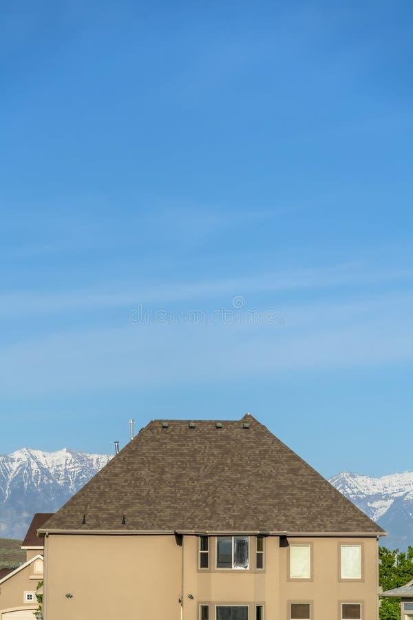 Het huis buiten met blauwe hemel en sneeuw dekte bergachtergrond op een zonnige dag af stock fotografie