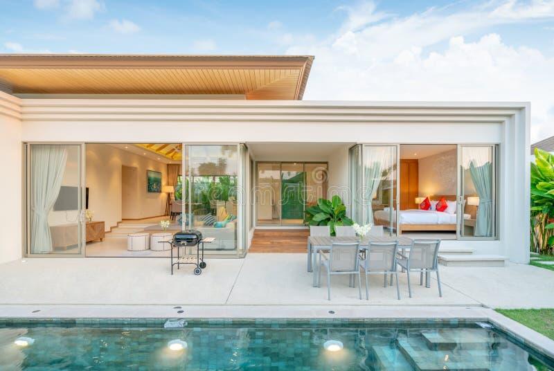 Het huis of het huis Buitenontwerp die tropische poolvilla met groen tonen tuiniert, zonbed, paraplu, poolhanddoeken, eettafel royalty-vrije stock foto's
