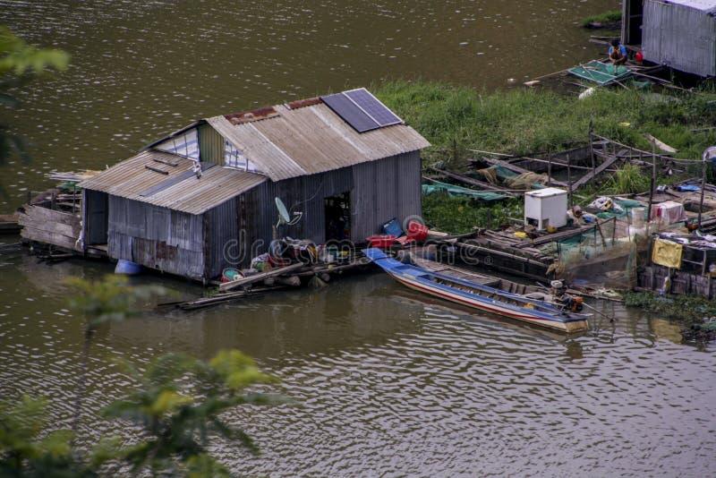 Het huis is een keet van tinbladen op het water in Vietnamees die visserijdorp wordt gebouwd op het water op Meerlak die wordt vo stock foto