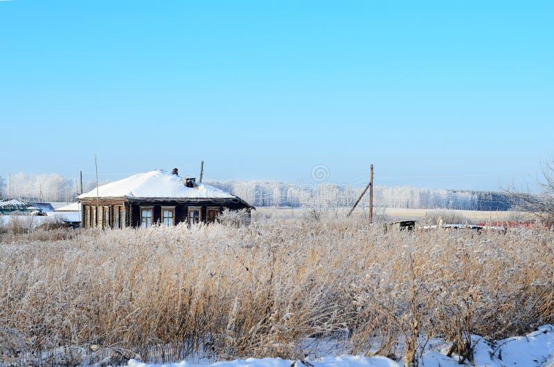 Het huis naast het opgedroogde gras op een de winterdag royalty-vrije stock afbeeldingen