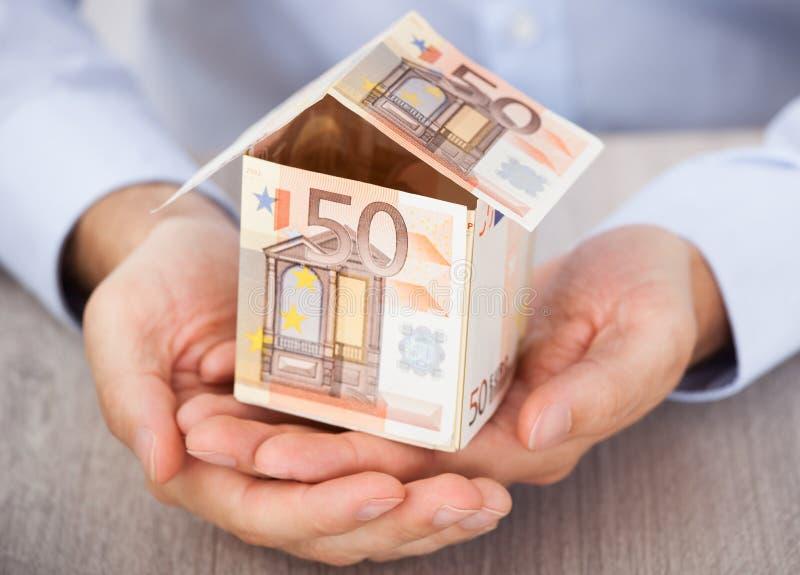 Het huis van de de handholding van de zakenman van euro nota's wordt gemaakt die royalty-vrije stock foto