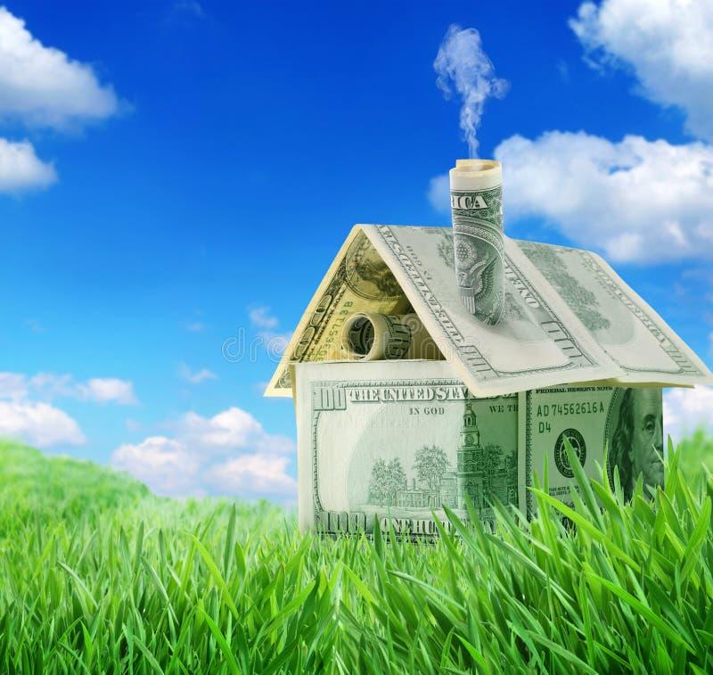 Het huis van de dollar in een groen gras stock afbeelding