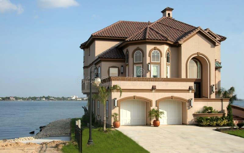 Het huis van de droom dichtbij het meer stock fotografie