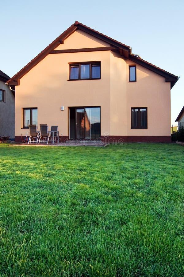 Het huis van de familie met een gazon bij dageraad royalty-vrije stock foto