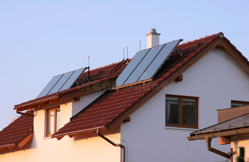 Het huis van de familie met zonnepanelen op het dak voor water het verwarmen stock foto