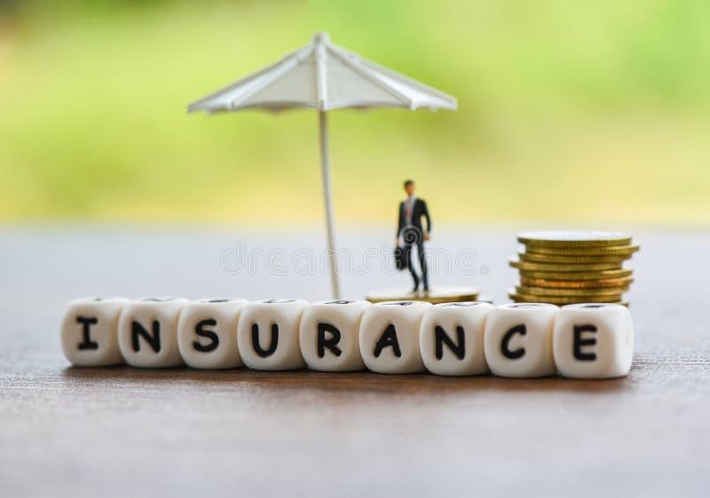 Het huis van de verkoopverzekering, auto, familieconcept/Witte paraplu die gouden muntstukveiligheid en zakenman beschermen stock afbeelding