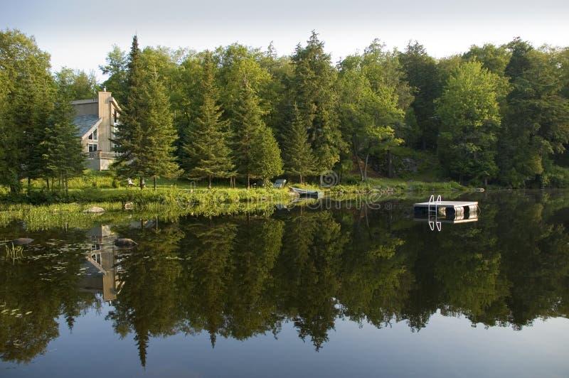 Het huis van de zomer op het meer stock afbeeldingen