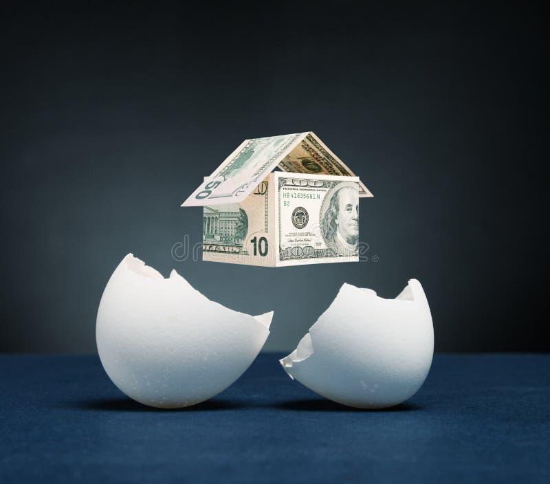 Het huis van geld verschijnt van het gebroken ei stock afbeeldingen