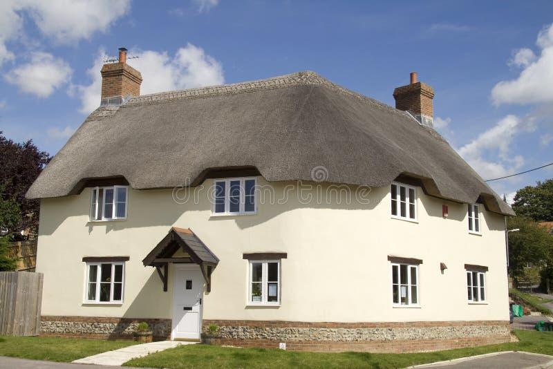 Het huis van het land met met stro bedekt dak royalty-vrije stock fotografie