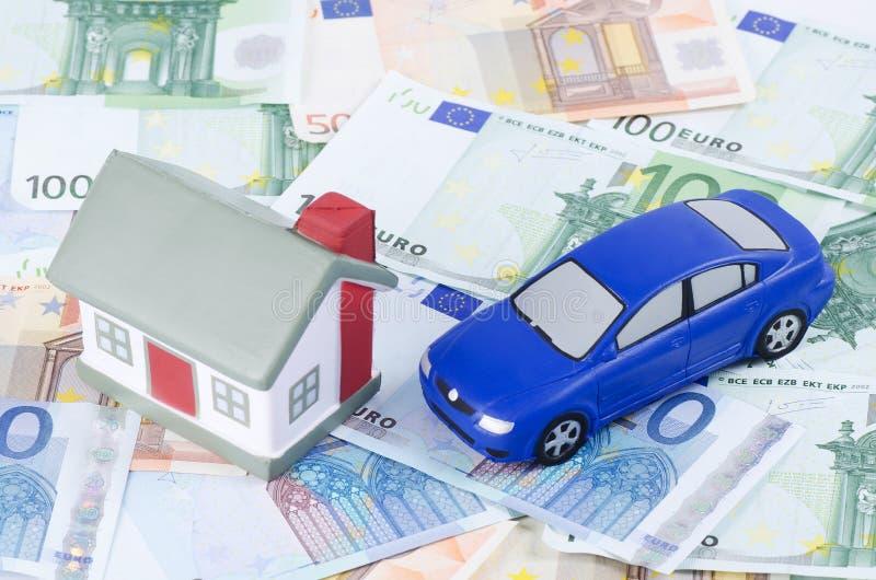 Het huis van het stuk speelgoed en de auto voor euro bankbiljetten stock foto