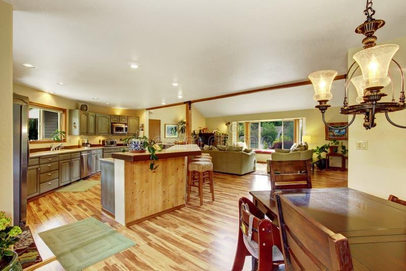 Het huisbinnenland met hardhoutvloeren en de open vloer plannen het tonen van eetkamer, keuken, en woonkamer stock foto
