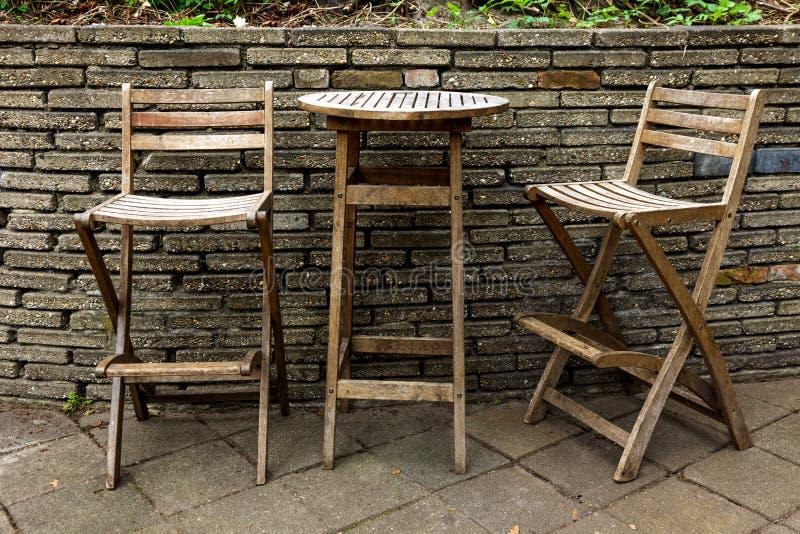 Het huistuin twee van het tuinmeubilair stoelen één oude uitstekende koffie van de lijst bruine bakstenen muur stock foto's