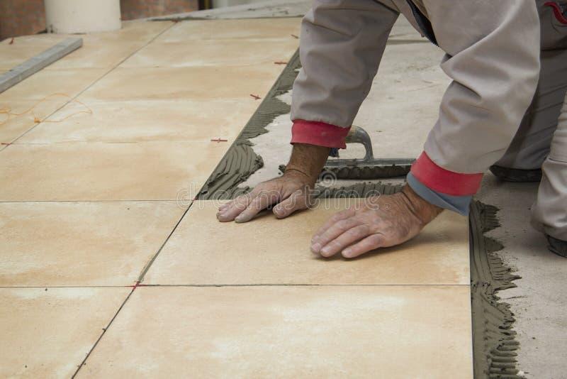 Het huisverbetering, vernieuwing - de bouwvakkertegelzetter betegelt royalty-vrije stock afbeelding