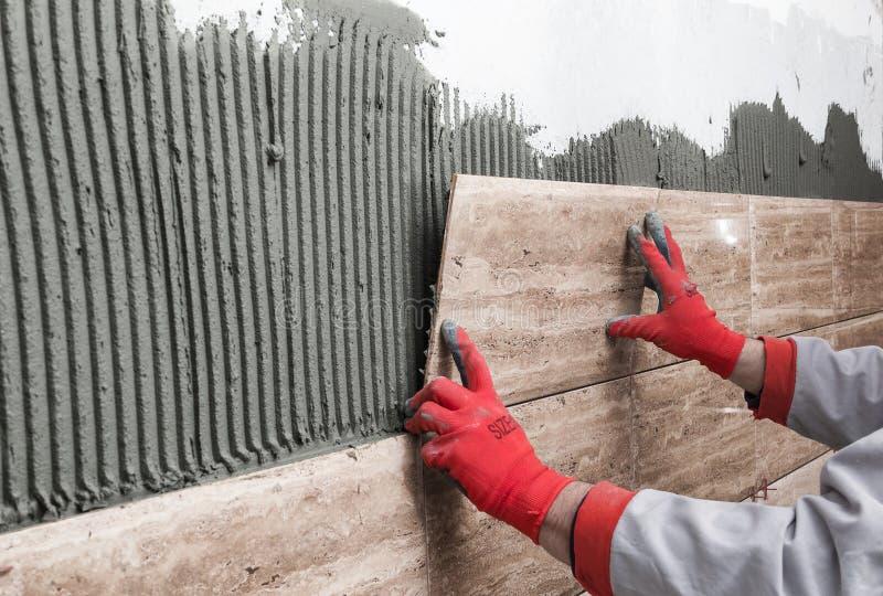 Het huisverbetering, vernieuwing - de bouwvakkertegelzetter is tili stock afbeelding