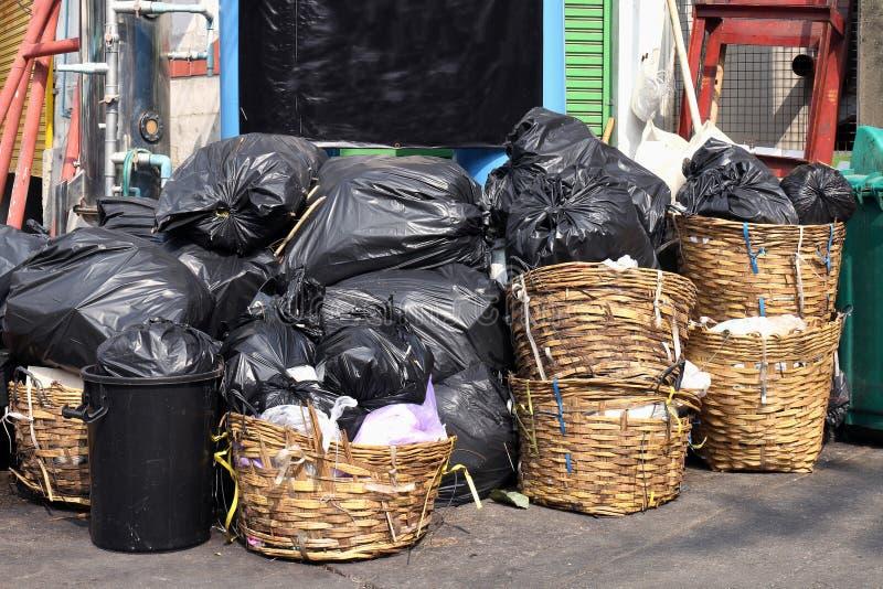 Het huisvuil is de stortplaats van stapelpartijen, velen het zwarte afval van huisvuil plastic zakken bij gang communautair dorp, royalty-vrije stock fotografie