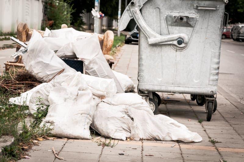 Het huisvuil in het wit doet dichtbij metaal dumpster op de straatverontreiniging de stad in zakken stock foto's