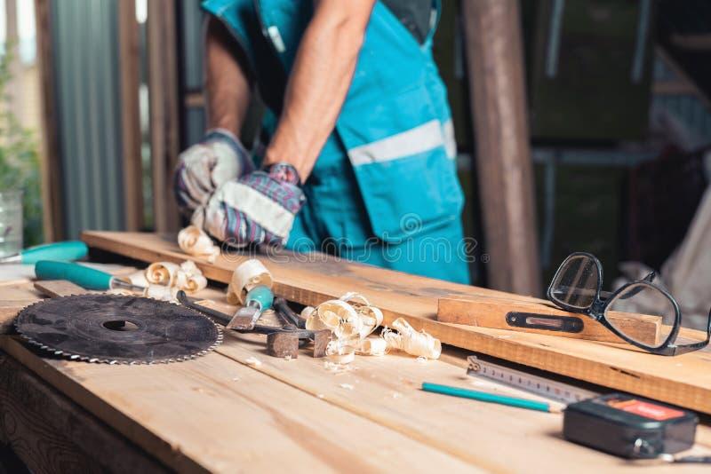 Het huisworkshop van de timmerman, houtbewerkingshulpmiddelen over de lijst, mens in handschoenen en overall met planer in het on stock afbeelding