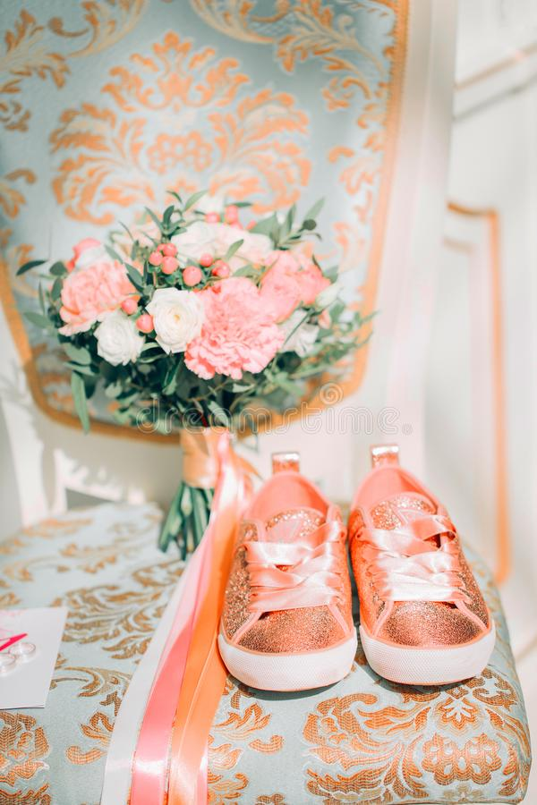 Het huwelijk bloeit, bruids boeket, Oranje tennisschoenen op een stoel in een helder binnenland stock fotografie