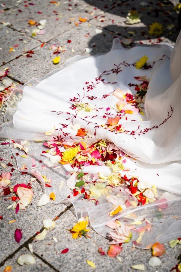 Het huwelijk, bloemblaadjes ligt op de huwelijkskleding stock foto