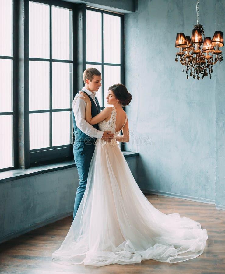 Het huwelijk is een plechtige dag Het modieuze jonge paar stellen tegen de achtergrond van luxueuze binnenlands De bruidegom koes stock afbeeldingen