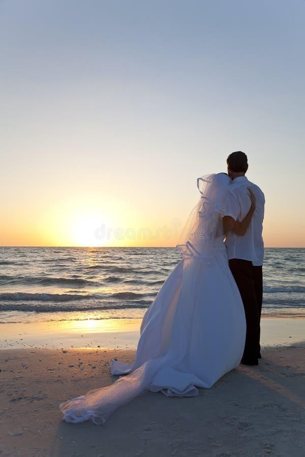 Het Huwelijk van het Strand van de Zonsondergang van het Echtpaar van de bruid & van de Bruidegom royalty-vrije stock afbeeldingen