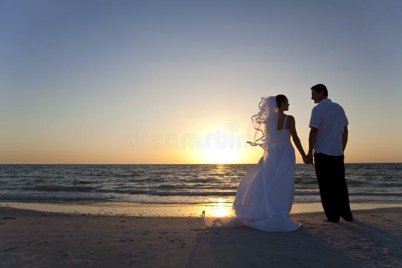 Het Huwelijk van het Strand van de Zonsondergang van het Echtpaar van de bruid & van de Bruidegom stock foto's