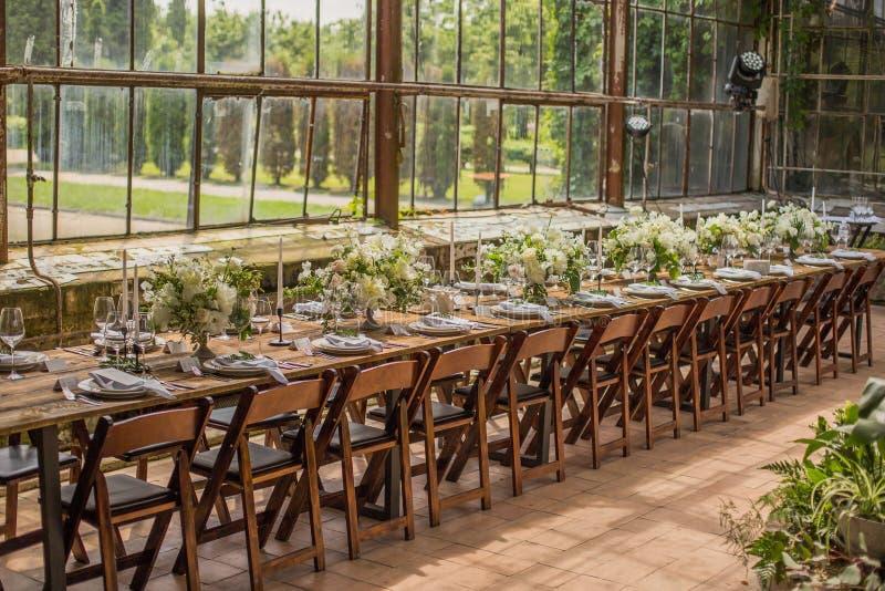 Het huwelijk is verfraaid in moderne stijl, met witte bloemen en heel wat groen in de ruimte met glasvensters in royalty-vrije stock afbeeldingen