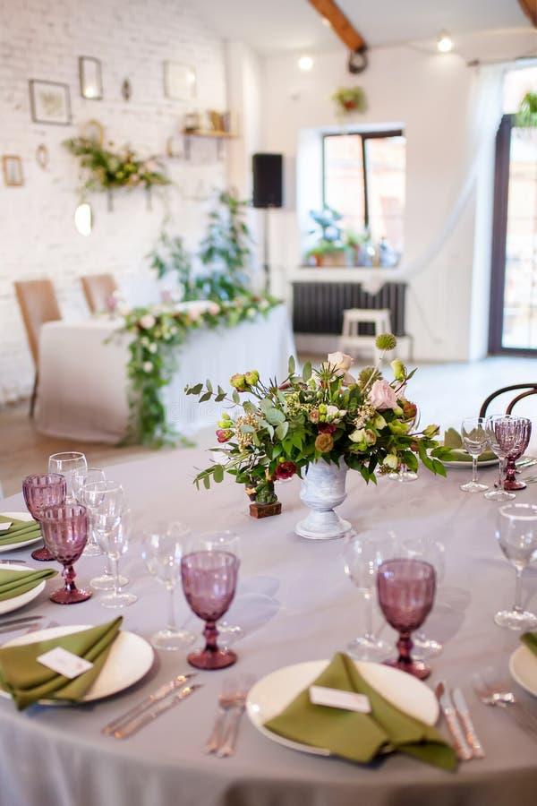 Het huwelijksbanket, zolderstijl, diende lijsten met bloemen en veel groen stock foto