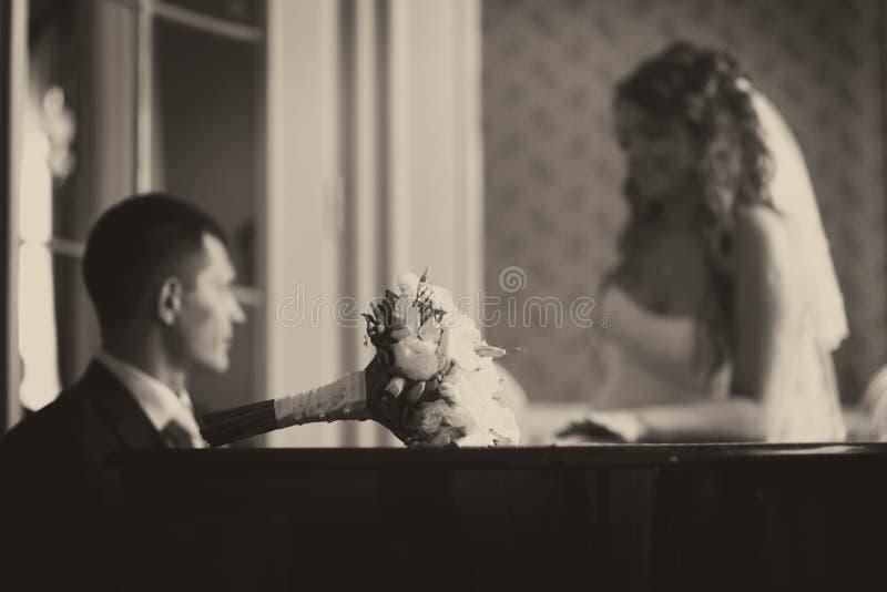 Het huwelijksboeket ligt op de piano terwijl bruidegomspelen voor een bruid royalty-vrije stock afbeelding