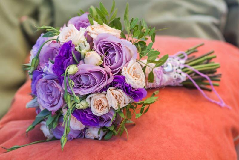 Het huwelijksboeket op een oranje hoofdkussen, boeket van bruid van roze roomnevel, nam struik, toenam purpere Geheugensteeg, vio stock afbeelding