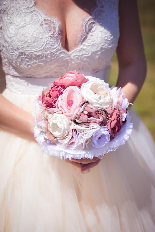 Het huwelijksboeket van de bruidholding royalty-vrije stock foto