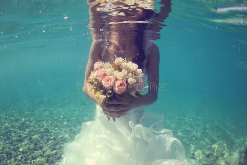 Het huwelijksboeket van de bruidholding onderwater royalty-vrije stock foto's