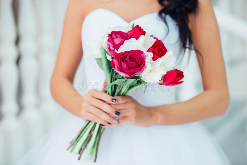 Het huwelijksboeket van Nice met rode bloemen in bruid` s handen stock foto