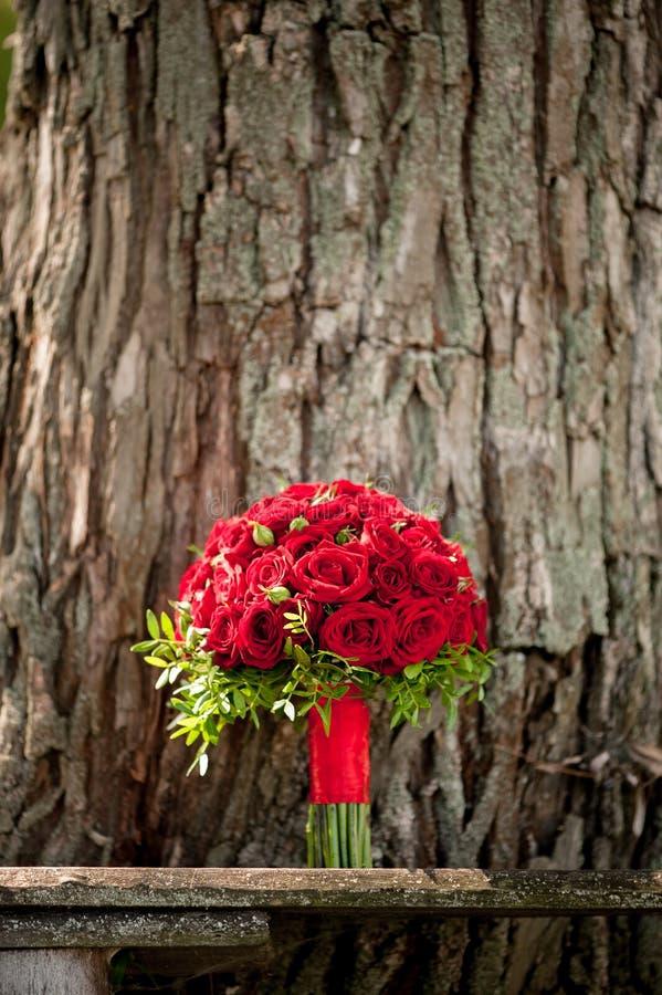 Het huwelijksboeket van rode rozen is op de achtergrond van boomschors stock afbeelding