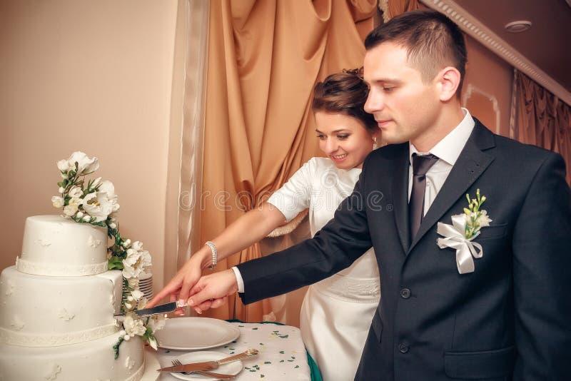 Het huwelijkscake van de jonggehuwdenbesnoeiing stock foto