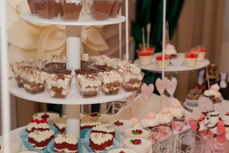 Het huwelijksdessert met heerlijke Cake knalt en verschillende snoepjes, suikergoedbar stock foto