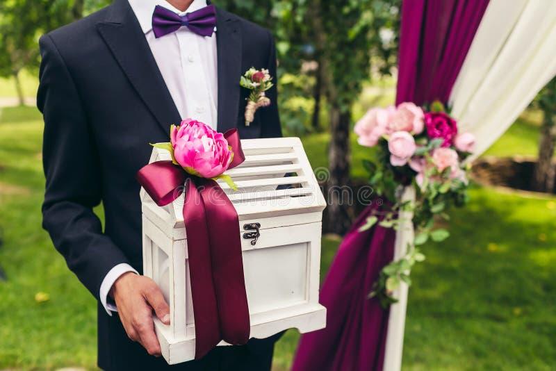 Het huwelijksdoos van de bruidegomgreep met bloem en lilac lint op huwelijk stock foto