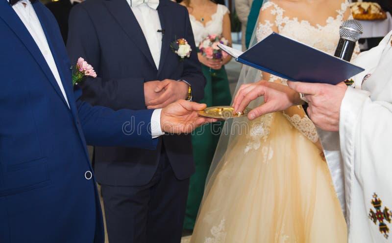 Het huwelijksechtpaar gaat trouwen in de orthodoxe christelijke kerk De priester heeft gouden ringen Traditionele ceremonie voor  stock foto