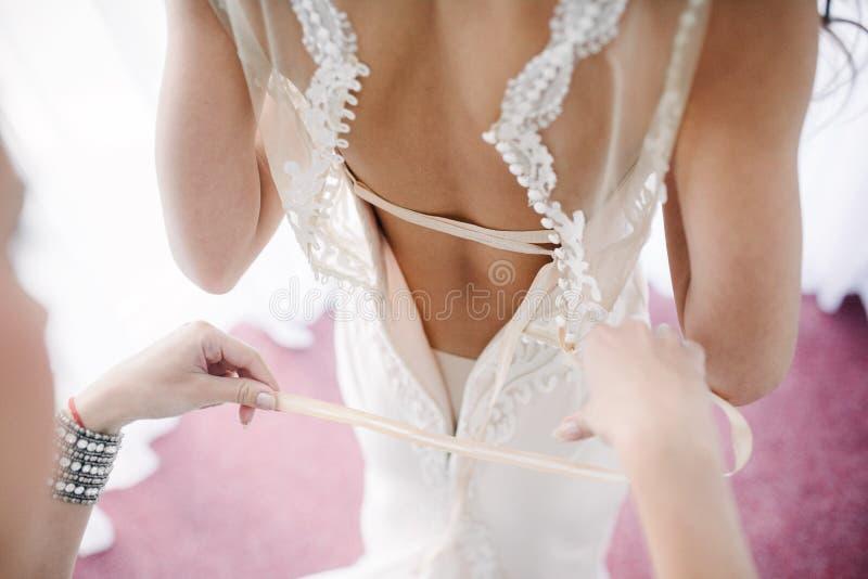 Het huwelijkskleding van het bruid witte kant Bruidhulp gezet op de huwelijkskleding stock foto