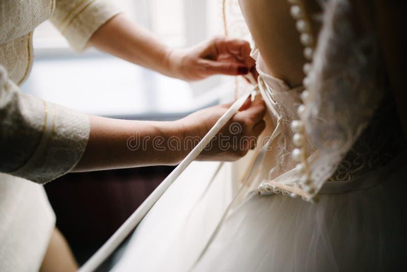 Het huwelijkskleding van het bruid witte kant Bruidhulp gezet op de huwelijkskleding royalty-vrije stock fotografie