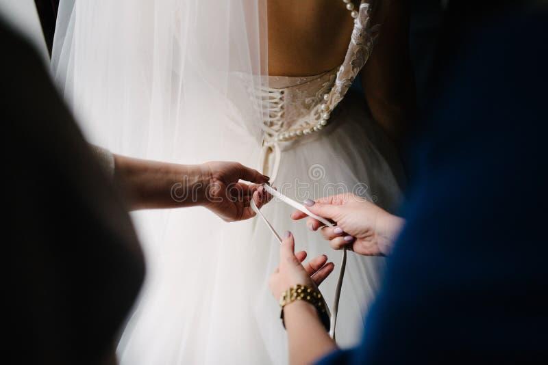Het huwelijkskleding van het bruid witte kant Bruidhulp gezet op de huwelijkskleding royalty-vrije stock afbeeldingen