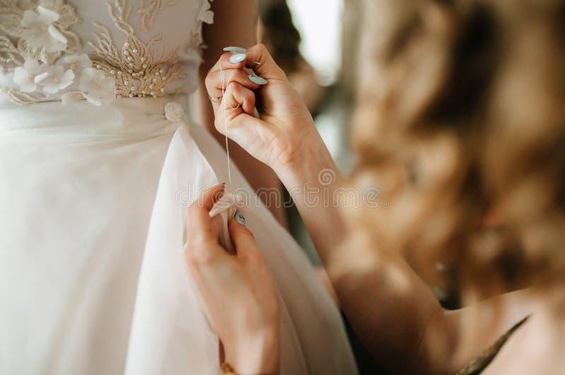 Het huwelijkskleding van het bruid witte kant Bruidhulp gezet op de huwelijkskleding royalty-vrije stock foto