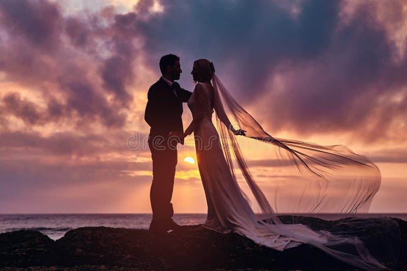 Het huwelijkspaar houdt elkaar status op het strand tegen de verbazende zonsondergang overhandigt royalty-vrije stock afbeeldingen