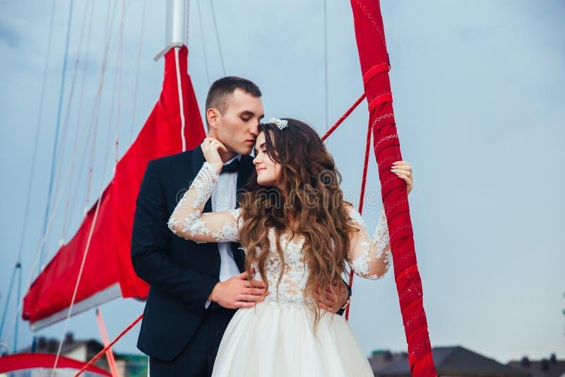 Het huwelijkspaar koestert op een jacht Schoonheidsbruid met bruidegom stock afbeelding
