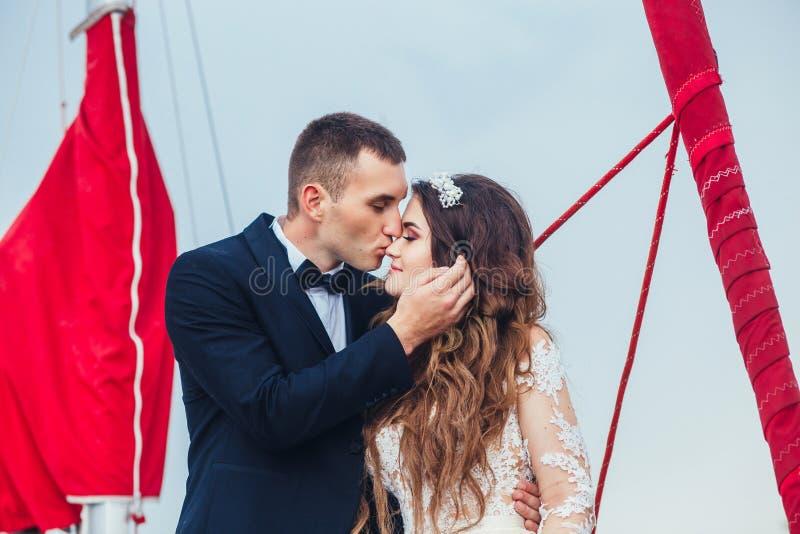 Het huwelijkspaar koestert op een jacht Schoonheidsbruid met bruidegom stock foto's