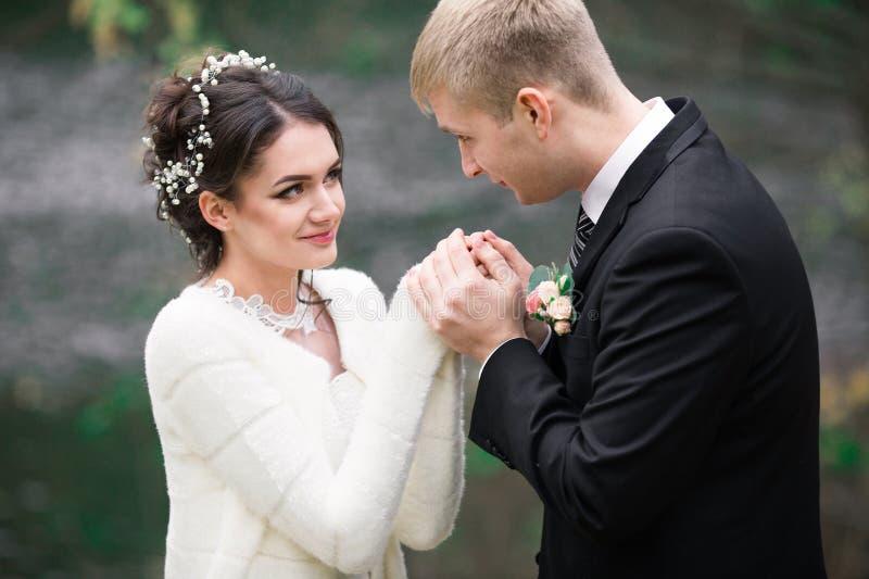 Het huwelijkspaar koestert in openlucht elkaar Mooi modelmeisje in witte kleding Mens in kostuum Schoonheidsbruid met bruidegom V stock foto