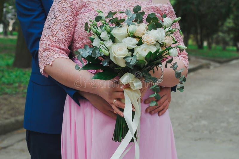 Het huwelijkspaar omhelst elkaar De handen van de bruidegom op de vrouw van de taillecurvy van de bruid in roze kantavondjurk Huw stock foto
