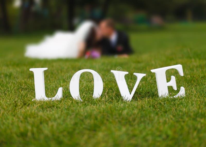 Het huwelijkspaar unfocused en het liefdewoord op het gras stock foto's